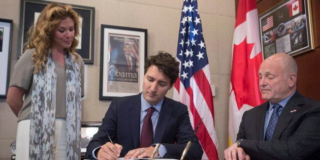 Sophie Gregoire Trudeau and the former ambassador of the United States to Canada Bruce Heyman look on as Prime Minister Justin Trudeau signs a book of condolence at the United States embassy in Ottawa on June 14, 2016.