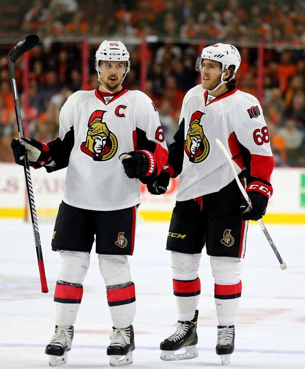Erik Karlsson #65 of the Ottawa Senators congratulates teammate Mike Hoffman #68 after he scored in the...