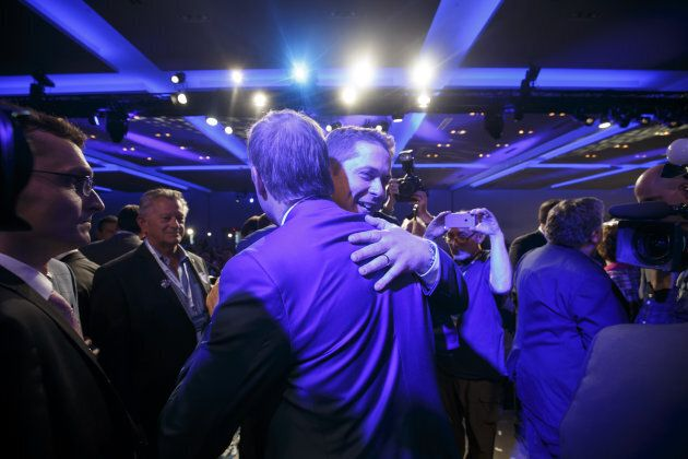 Andrew Scheer, leader of Canada's Conservative Party, center right, hugs Maxime Bernier, at the party's...