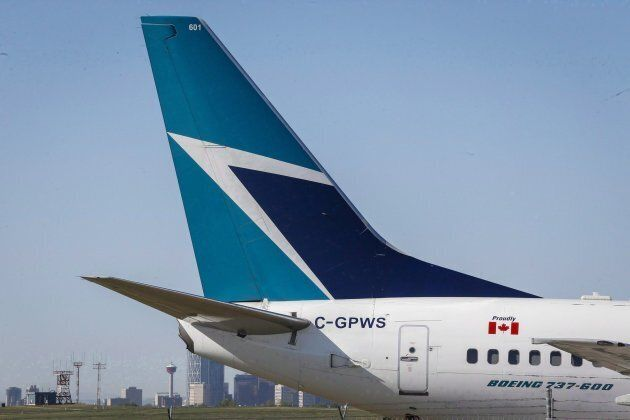 The tail of a WestJet plane is seen dwarfing the Calgary skyline before the airline's annual meeting...