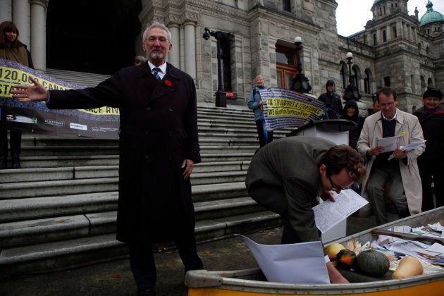 MLA Leonard Krog, (left), looks on as Sierra Club B.C. Galen Armstrong gathers petitions, postcards and...