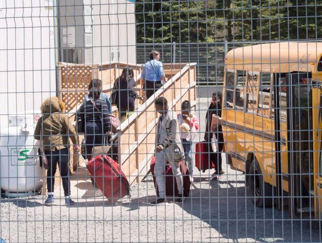 A group of asylum seekers arrive at the temporary housing facilities at the border crossing on May 9,...