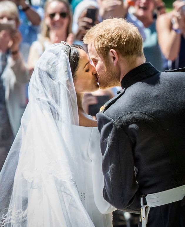 Prince Harry and Meghan Markle kiss on the steps of St George's Chapel in Windsor Castle after their...