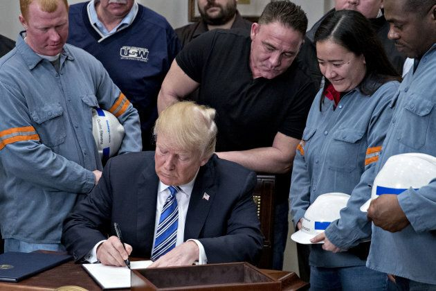 U.S. President Donald Trump signs a proclamation on adjusting imports of steel into the United States next to steel and aluminum workers in the Roosevelt Room of the White House in Washington, D.C., on March 8, 2018.