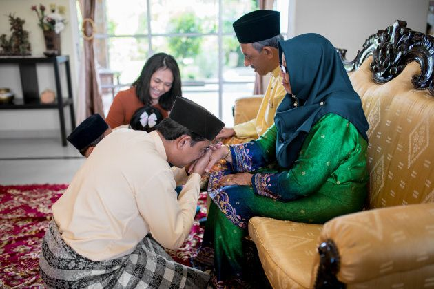 Son asking his mother for forgiveness as part of the the Islamic celebration of Eid al-Fitr in Malaysia.