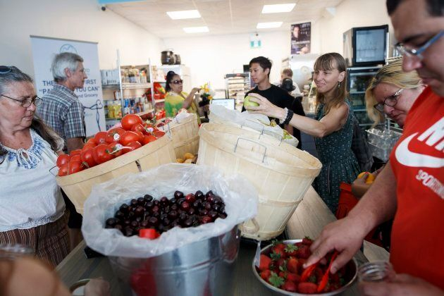People are seen shopping for produce at Feed it Forward's Pay-what-you-can grocery store in