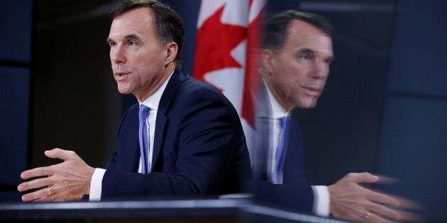 Finance Minister Bill Morneau is reflected on a monitor while speaking during a news conference about...