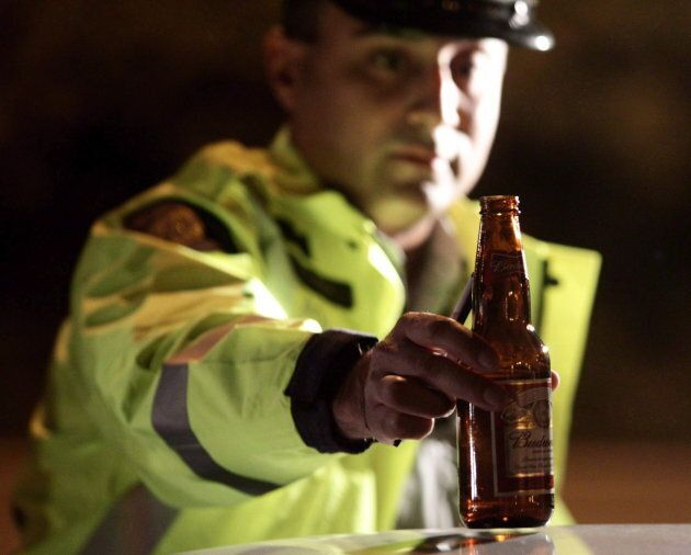 RCMP Cnst. Faz Majid removes an open bottle of beer from a motorist's car during a roadside check in...