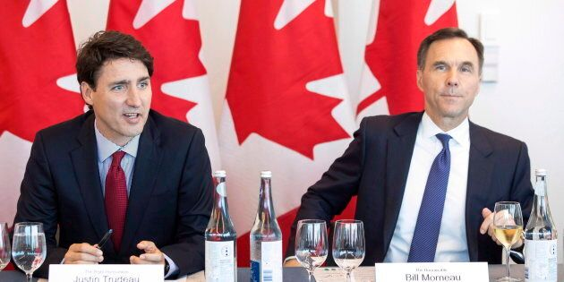 Prime Minister Justin Trudeau (left) sits next to Federal Finance Minister Bill Morneau during a round...
