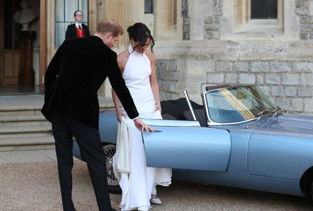 Prince Harry helps his new bride, the Duchess of Sussex, into the car as they leave Windsor Castle after...