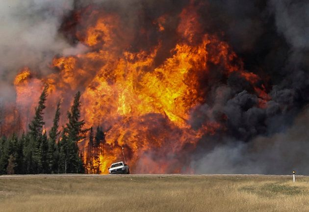 Smoke and flames from the wildfires erupt behind a car on the highway near Fort McMurray, Alta. on May 7, 2016.