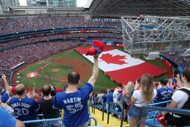 An overhead view of the Rogers Centre as a large Canadian flag is unfurled for Canada Day on July 1,