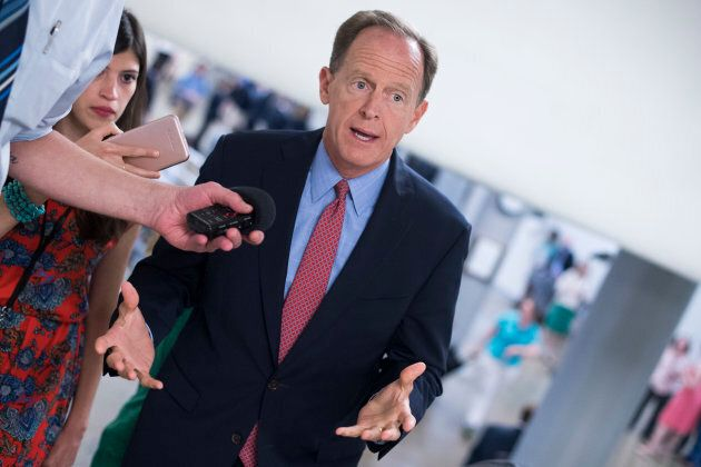 Sen. Pat Toomey, R-Pa., talks with reporters in the Capitol's Senate subway before the Senate Policy...
