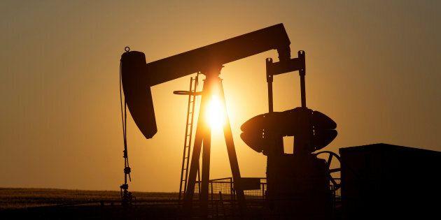 An oil pump jack pumps oil in a field near Calgary on July 21,