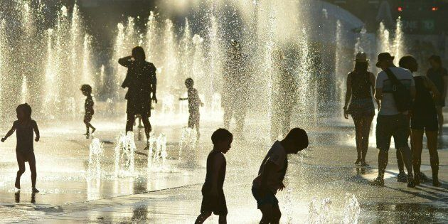 Children play in the water fountains at the Place des Arts in Montreal on a hot summer day July 3,
