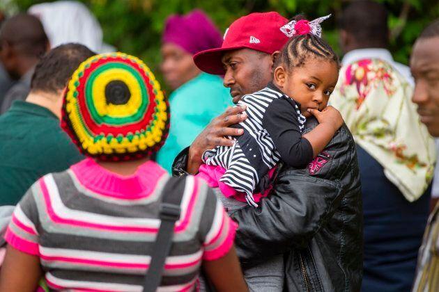 A long line of asylum seekers wait to cross the Canada-U.S. border near Champlain, N.Y. on Aug. 6,