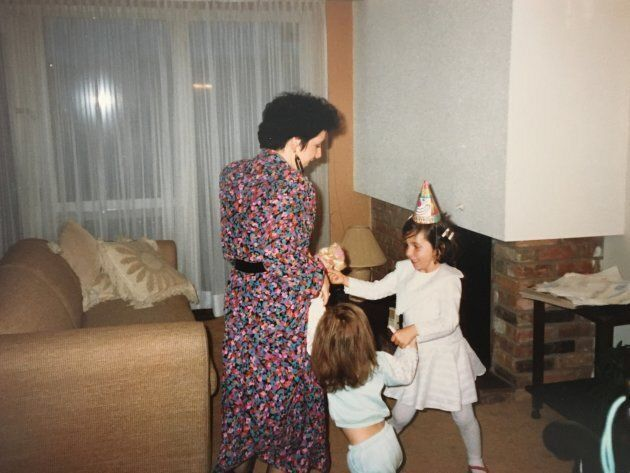 The author, in a birthday hat, dancing with her mother and younger sister in their spectacularly 80s-beige living room.