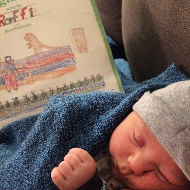 "The author's newborn son enjoying ""Six Little Ducks"" while dozing with his mama."