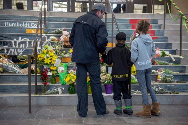 People gather at a memorial set up on the stairs that lead to Elgar Petersen Arena in Humboldt, Sask....