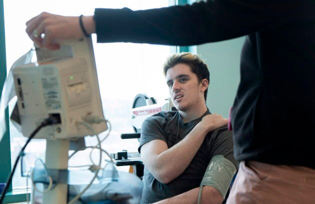 Humboldt Broncos survivor Ryan Straschnitzki has his blood pressure taken during a physiotherapy session at the Shriners Hospital in Philadelphia on June 25, 2018.