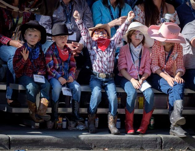 Young spectators cheer during the Calgary Stampede parade on July 6, 2018.