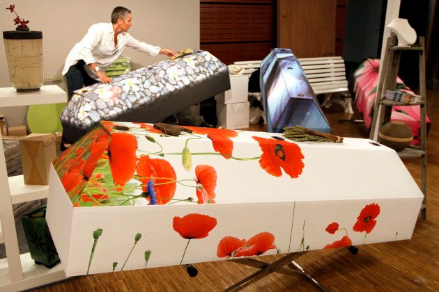 Brigitte Sabatier prepares her stand of bio-degradable cardboard coffins during media day at the 'Salon...