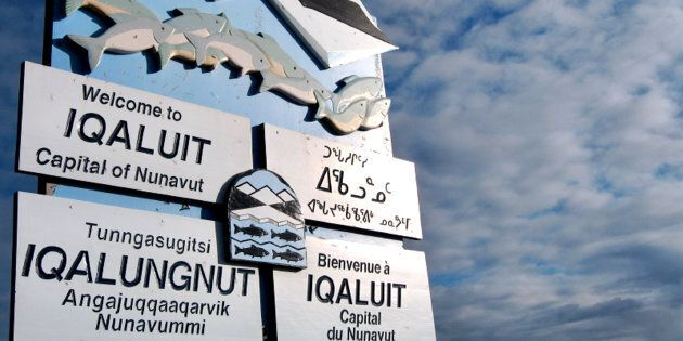 A sign written in various languages, clockwise from top left, English, Inuktitut (syllabic), French,...