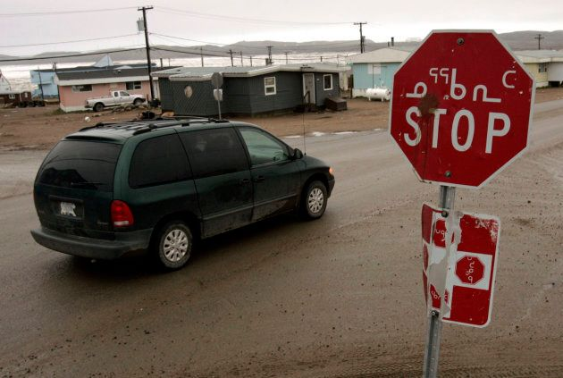 A van passes a stop sign in English and Inuktitut in Iqaluit, July 7,