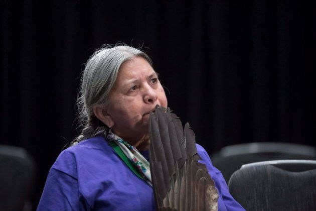 A woman holds a eagle feather as she listens to Anni Phillips give her testimony during the National Inquiry of Missing and Murdered Indigenous Women and Girls in Richmond, B.C. on April 4, 2018.