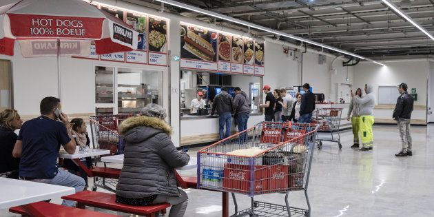 Customers line up for ready cooked food at the cafe inside a Costco Wholesale Corp. store in Villebon-sur-Yvette,...