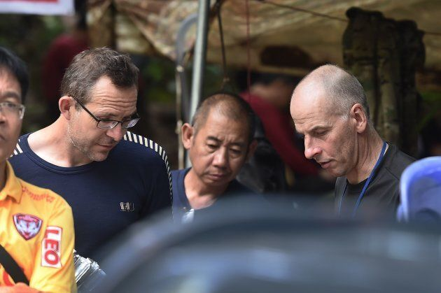 British divers John Volanthen, left, and Richard William Stanton, right, are seen with Thai rescue personnel...