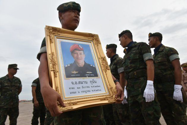 A Royal Thai Navy soldier carries a portrait of Saman Gunan, a former navy SEAL who died in the Tham...