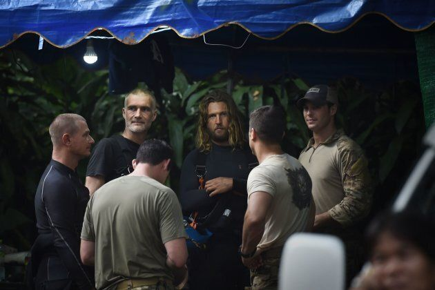 A group of foreign divers and U.S. soldiers, wearing light-coloured shirts, gather at the Tham Luang...