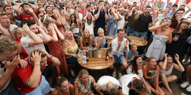 Fans react to a near miss from England while watching coverage of the FIFA World Cup 2018 quarter-final...