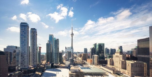 A high-resolution panoramic image of Toronto's city centre skyline, with the CN Tower in the centre.