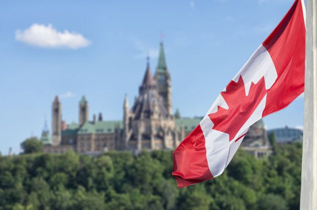 Canadian flag waving with Parliament Buildings hill and Library in the background.