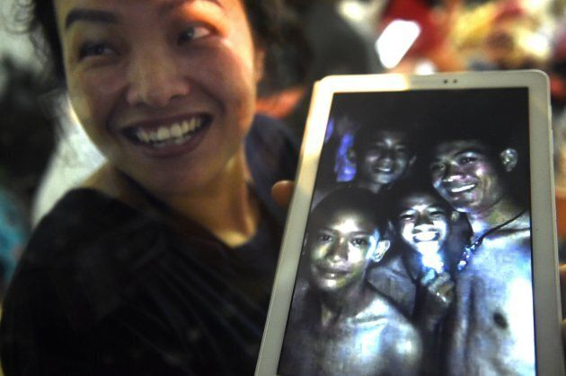 Thanaporn Promthep, mother of one of the 12 missing boys, displays an image believed to have been taken...