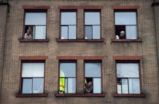 Residents of a single room occupancy hotel (SRO) watch from windows in the Downtown Eastside of Vancouver, B.C.