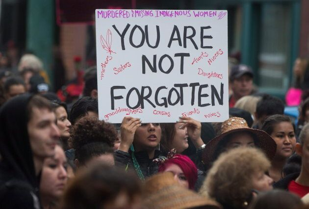 A woman holds a sign as hundreds of people march through the Downtown Eastside during the 25th annual...