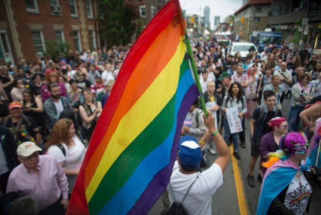 A man holds a Pride flag near the stage in Toronto on June 22,