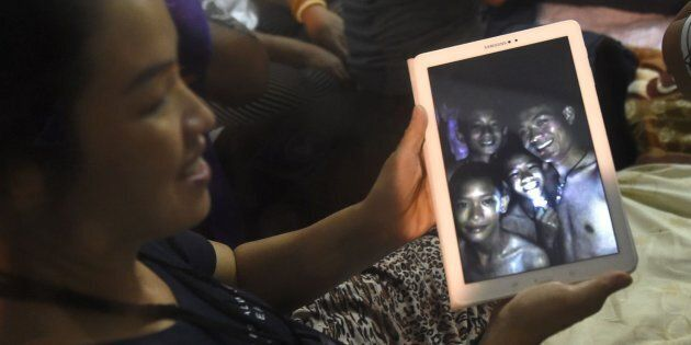 A happy family member shows the latest pictures of the missing boys taken by rescue divers inside Tham...