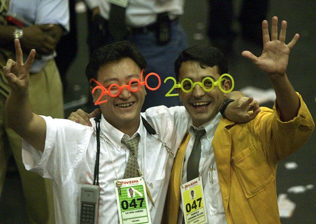 Stock traders wearing Y2K glasses celebrate at the last trading day 1999, where closed up with the historic...