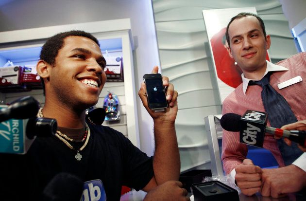Jordon Brown, the first buyer of the new Apple iPhone 3G in Toronto, shows off his phone July 11,