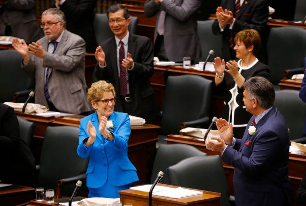 Ontario Premier Kathleen Wynne applauds Ontario Finance Minister Charles Sousa as the provincial budget is distributed at Queens Park in Toronto on May 1, 2014.