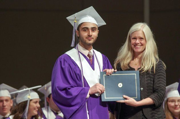Yasser Al Asmi receiving the Roméo LeBlanc scholarship from the mayor of Moncton, Dawn Arnold, during his graduation ceremony.