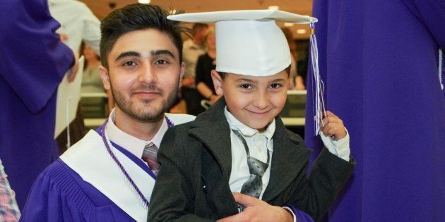 Yasser Al Asmi, 18, smiles with his younger brother at his graduation from Moncton High School.