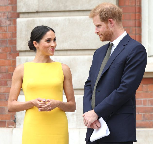 Meghan Markle in a yellow Brandon Maxwell sheath dress with a modified boatneck, with husband Prince...