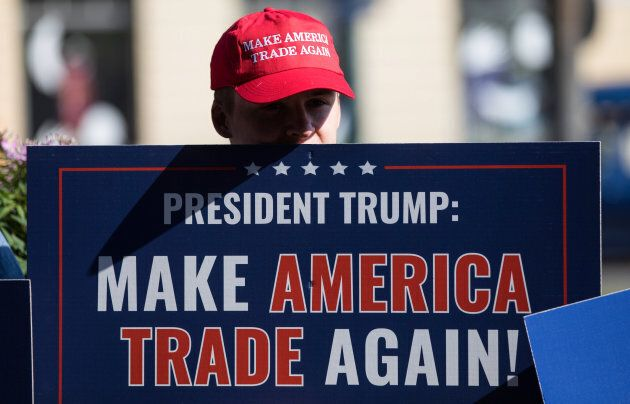 A demonstrator wears a 'Make America Trade Again' hat close to the Presidential Palace in Helsinki on...