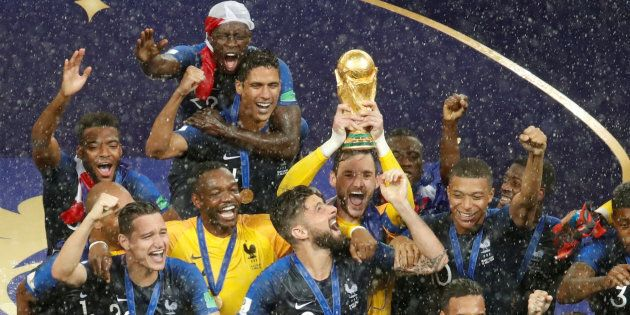 France's Hugo Lloris lifts the trophy as his team celebrates winning the World Cup in Moscow on Sunday