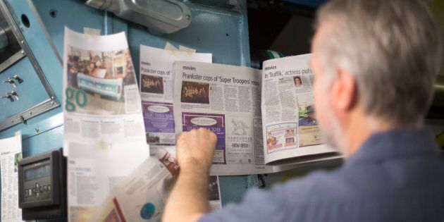 Foreman John Shamrock checks the color on a page of newspaper while printing the daily edition of The...